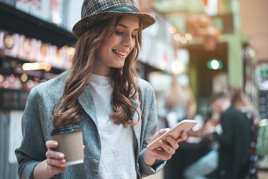 Grinning pretty woman looking at phone. She is standing in trendy hat with cup of hot drink outside