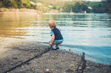 Toddler boy playing by the water