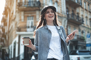 Smiling lady in trendy hat is listening to music with smartphone and earphones. She is standing outdoors with cup of coffee