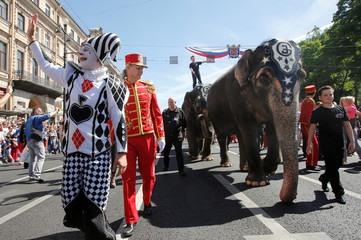 A participant poses for a picture while escorting elephants during the City Day celebrations in St. Petersburg