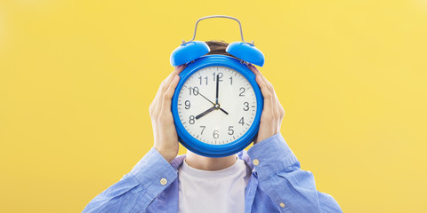 young person with clock or alarm, concept of time and punctuality