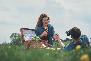 Glad married couple is having picnic on grassland. Lady is giving glass of wine to husband while he is photographing her on camera. Family entertainment concept