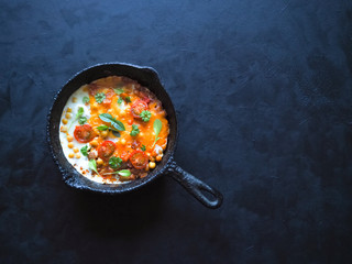 Scrambled eggs with chickpeas and tomatoes on an old pan. Top view with copy space.