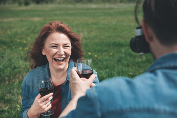 Smile. Portrait of happy mature woman is laughing while drinking wine on the meadow. Man is taking photo of her