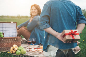 Focus on male arms holding a gift box behind his head. Excited woman is looking at husband with anticipation and smiling. Couple is celebrating anniversary on the grassland