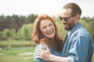 Portrait of joyful red-haired woman enjoying hug of her man and smiling. Picturesque lake is on background. Copy space