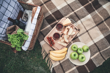 Papiers peints Pique-nique Top view close up of two glasses of red wine with bread and cheese near tomatoes on wooden tray. Bananas and apples on blanket. Picnic basket on the lawn