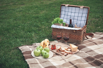 Romantic picnic in the nature. Two glasses of wine, fruits and vegetables on blanket on the grass