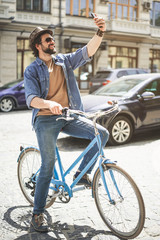 Full length of cheerful stylish man sitting on bicycle and photographing himself on mobile phone