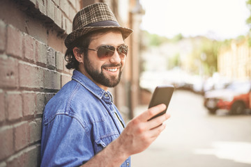 Portrait of joyous male person in elegant headdress and sunglasses posing near wall outdoors. He is looking at cellphone in hand with pleasure. Copy space in right side