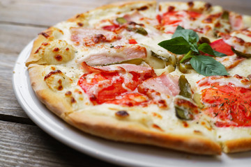 Italian hot pizza with bacon,tomatoes and gherkins, close up. Fast food, restaurant, pizzeria, food photo,pizza delivery concept