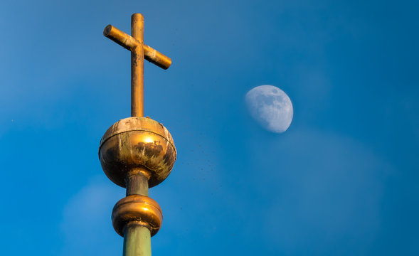 The top of the medieval chapel of the ancient town of Hurden with clear blue skies and nearly a full moon in the background, Upper Zurich Lake (Obersee), Schwyz, Switzerland