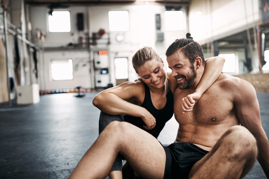 Young couple hugging on a gym floor after working out