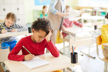 Pensive student of elementary school leaning over his copybook while ticking right answers in test