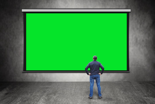 Man stands in front of big empty green screen