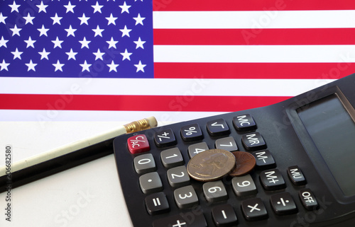 Coin Of United Stage America On Calculator And Pencil White Floor With Usa Flag