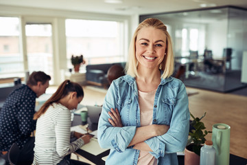 Young businesswoman smiling with coworkers sitting in the backgr