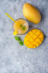 Healthy drink. Mango smoothie on concrete table. Top view. Tropical fruit juice. Vertical photo.
