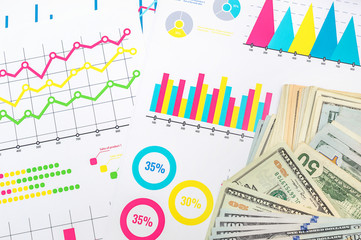Money on multicolour financial graphs and charts. Business concept.