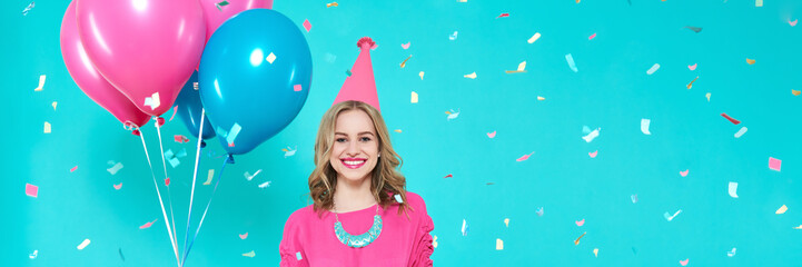 Gorgeous birthday girl in party outfit holding colourful balloons. Attractive trendy teenager celebrating birthday. Party and flying confetti on pastel blue background. Web banner.
