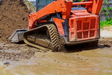 Wheel loader Excavator with backhoe unloading earth at eathmoving works construction site quarry