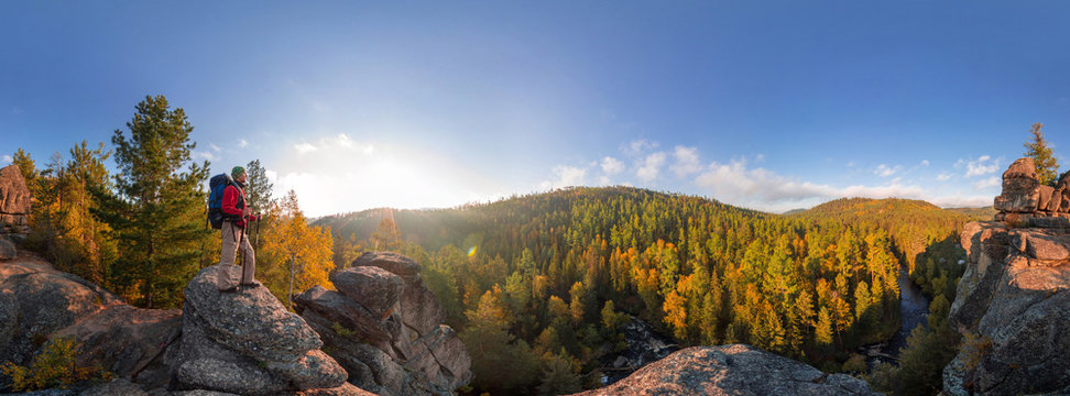 Backpacker on top of a rock fall at dawn. Cylindrical panorama 360 degrees