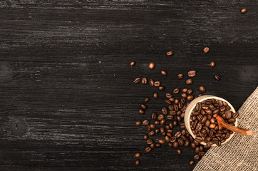 Coffee beans scattered from a wooden pot full of coffee and wooden spoon on black table surface background with copy space.