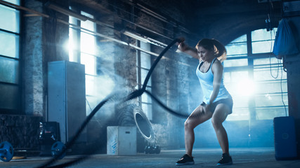 Athletic Female in a Gym Exercises with Battle Ropes During Her Cross Fitness Workout/ High-Intensity Interval Training. She's Muscular and Sweaty, Gym is in Deserted Factory. Cold Ambient.