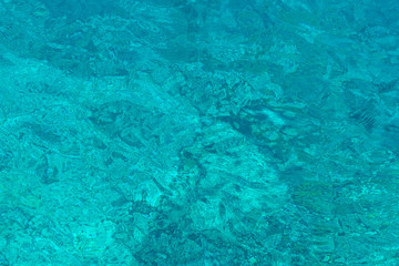 Saturated turquoise textured sea water surface lit with sunlight