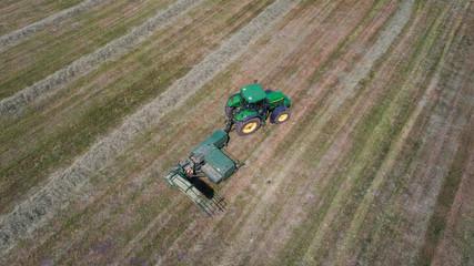 Heu Ernte  auf dem Feld mittels Heupresse und Traktor,
