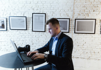 Business man working on laptop computer at coworking open office.