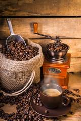 chicchi di caffè in sacco di iuta con macinino di legno e tazzina di caffè fumante