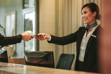Smiling receptionist attending hotel guest