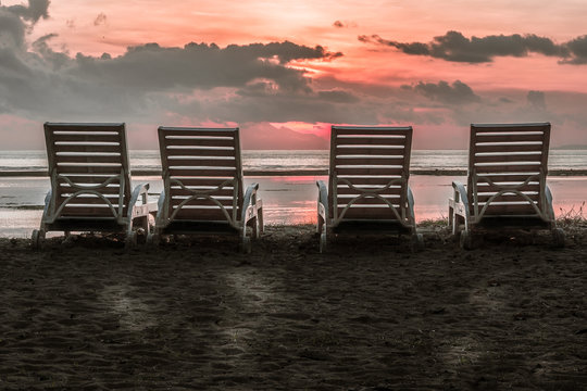 The backside of four chairs close to the beach in the tropical sunset