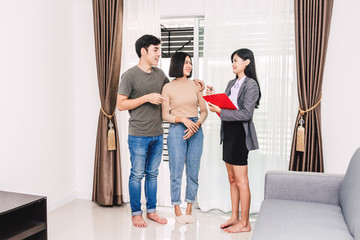 Real estate agent holding document and talk with young couple in a house for sale. business and real estate concept