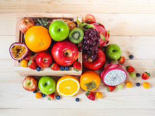 Colorful fresh fruits and vegetables on wood background, healthy eating concept.