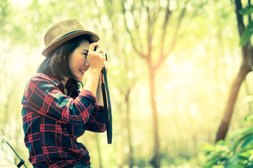 asian woman take photo in forest camp travel concept