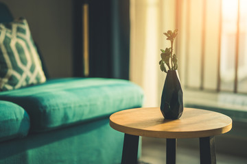 flower vase on wooden table and soft sofa evening light time
