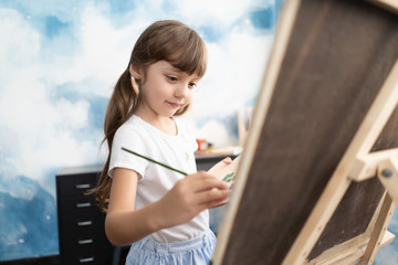 Portrait of a beautiful liitle girl painting in at her home.Concept of early childhood education, happy family, parenting