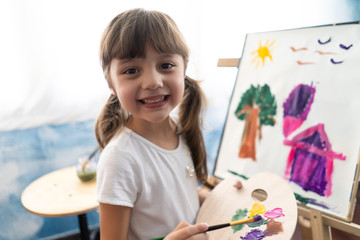 Close-up Portrait of a beautiful liitle girl painting in at her home.Concept of early childhood education, happy family, parenting