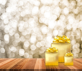 Golden present on wood table top with blur sparkling gold bokeh light background,Gift giving concept,Leave space for adding text for new year or Christmas card.
