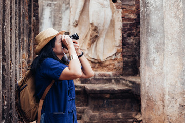 Asian tourist woman taking photo of ancient of Thai temple architecture at Sukhothai Historical Park,Thailand. Female traveler in casual thai Mauhom shirt style visiting city.Summer holiday vacation.