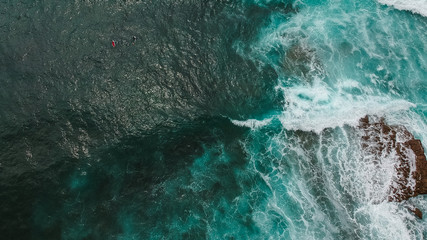 Aerial view from a surf spot with waves and a two surfers in Ericeira, Portugal
