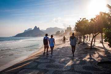 People walk on the famous sidewalk of Ipanema beach by sunset Wall mural