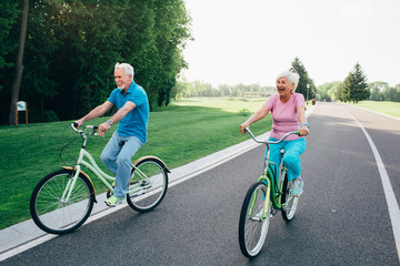 Older Caucasian couple riding bicycle