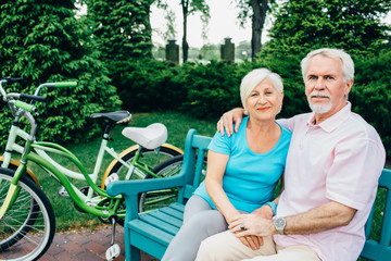 portrait of an elderly couple sitting in a city park