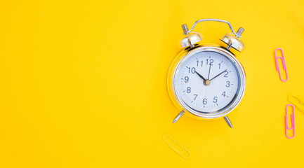 back to school or office styed scene with alarm clock and copy space on yellow background banner