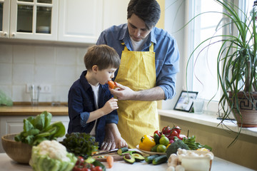 father and son cooking salad