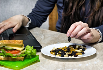 A girl works behind a laptop and takes from a plate dried fruits, a sandwich, a snack at work, close-up