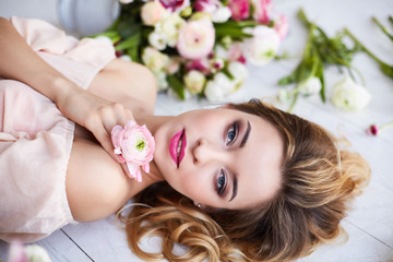 Beautiful young woman with make-up and curls. The girl's face is in flowers.